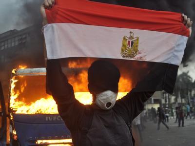 Die ägyptische Flagge vor dem Hintergrund eines brennenden Wagens: Kairo kommt nicht zur Ruhe. Foto: Ahmed Assadya