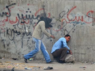 Demonstranten auf dem Tahrir-Platz erholen sich von einer Tränengas-Attacke der Sicherheitskräfte. Foto: Mohamed Omar
