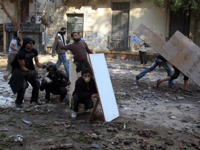 Junge Männer werfen Steine auf Sicherheitskräfte und schützen sich mit Brettern. Foto: Khaled Elfiqi