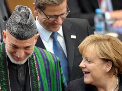 Der afghanische Präsident Hamid Karsai, Außenminister Guido Westerwelle und Bundeskanzlerin Angela Merkel (v.l.n.r.) auf der Afghanistan-Konferenz. Foto: Federico Gambarini
