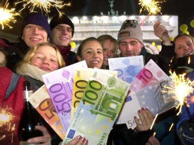 Mit übergroßen Euroschein-Nachbildungen feiern Jugendliche in der Silvesternacht am 1.1.2002 vor dem Brandenburger Tor in Berlin die Einführung der neuen Währung. Foto: Stephanie Pilick/Archiv