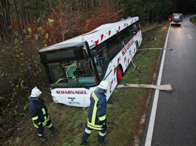 Ein Linienbus liegt nahe Herrieden (Mittelfranken) neben der Fahrbahn im Graben. Bei dem Schulbus-Unfall sind am Montagmorgen sieben Kinder verletzt worden. Foto: Daniel Karmann
