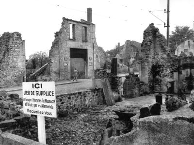 Blick auf die Ruinen von Oradour-sur-Glane (Frankreich) und eine Gedenktafel, deren Text lautet:«Gedenkstätte - Eine Gruppe von Männern wurde hier von den Deutschen massakriert und verbrannt - Besinnt Euch».