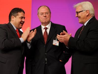 Der SPD-Vorsitzende Sigmar Gabriel (l) und der Vorsitzende der SPD-Bundestagsfraktion, Frank-Walter Steinmeier (r), applaudieren dem ehemaligen Bundesfinanzminister Peer Steinbrück auf dem Bundesparteitag. Foto: Sebastian Kahnert