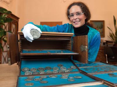 Hausmeisterin Tanja Höls mit dem von ihr entdeckten Silberschatz in der Staatlichen Bibliothek in Passau. Foto: Armin Weigel