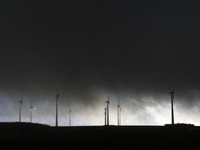 Windräder unter einem von Sturmwolken verdunkelten Himmel. Foto: Uwe Zucchi/Archiv
