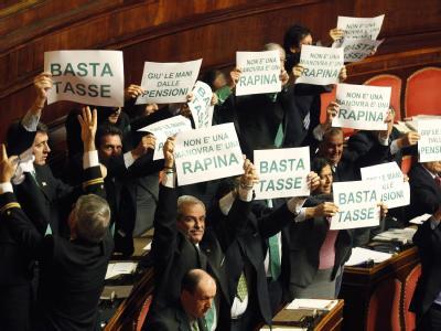 Abgeordnete der Lega Nord halten im Senat Protestplakate gegen das Sparpaket von Ministerpräsident Monti hoch. Foto: Alessandro di Meo