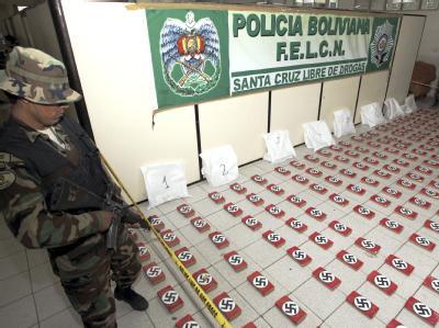 Ein Soldat der bolivianischen Anti-Drogen Task Force steht in Santa Cruz de la Sierra neben Kokainpäckchen mit Hakenkreuzen. Foto: El Deber