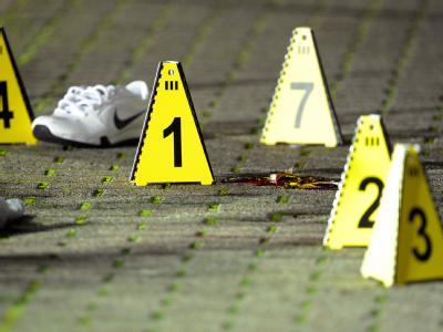Bottrop: Nummerntafeln der Spurensicherung neben einer Blutlache und einem Schuh. Foto: Marius Becker