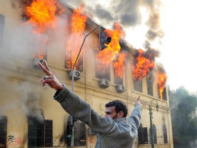 Ein Demonstrant zeigt das Siegeszeichen vor einem brennenden Gebäude in der Kasr al-Aini Straße in Kairo. Foto: Mohamed Omar