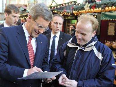 Bundespräsident Christian Wulff gibt auf dem Weihnachtsmarkt vor dem Frankfurter Römer ein Autogramm. Foto: Boris Roessler