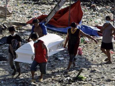 Philippiner mit dem Sarg eines Opfers der Flutkatastrophe. Foto: Francis R. Malasig