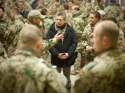 Verteidigungsminister Thomas de Maizière spricht im Feldlager der Bundeswehr in Kundus mit Soldaten. Foto: Michael Kappeler