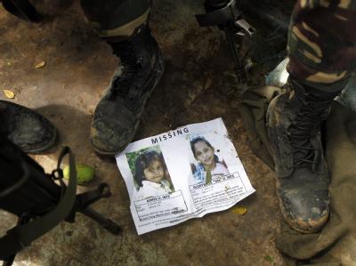 Soldaten betrachten das Bild einer Vermissten nach der Sturzflut im Süden der Philippinen. Foto: Francis R. Malasig