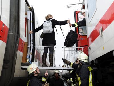Reisegäste eines ICE der Deutschen Bahn steigen nach einem Schaden an der Bremse bei Gardelegen (Sachsen-Anhalt) in einen Ersatzzug um. Foto: Hermann Hay
