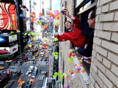 Tim Tompkins, Chef der Times Square Alliance(L), und Jeffrey Strauss von Countdown Entertainment testen am New Yorker Times Square schon einmal die Windverhältnisse für den Konfetti-Regen. Foto: Justin Lane