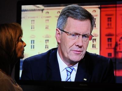 Eine Frau schaut das Interview mit Bundespräsident Wulff. Foto: Holger Hollemann