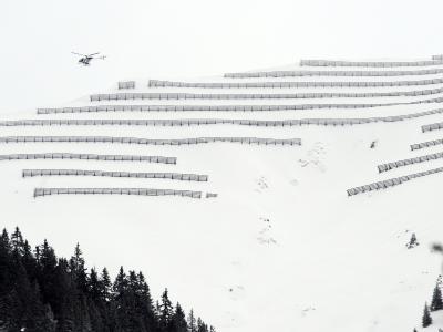Ein Hubschrauber mit einem Lawinenexperten an Bord überfliegt die bayerischen Alpen. Foto: Patrick Seeger