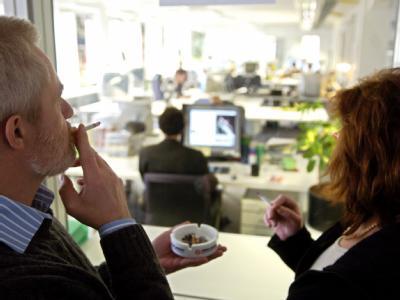 Raucher hinter einer Trennwand zu einem Großraumbüro: Wirtschaftsverbände fordern die Einführung komplett rauchfreier Arbeitszeiten. Foto: Jan Woitas