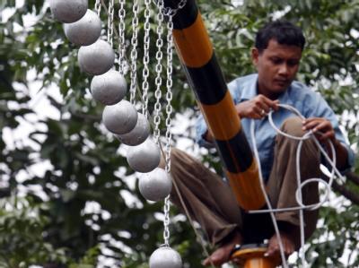 Betonkugeln baumeln an einem Gerüst an einer Bahnstrecke in der indonesischen Provinz Jawa Barat. Damit sollen Pendler davon abgehalten werden, auf den Zugdächern zu reisen. Foto: Bagus Indahono