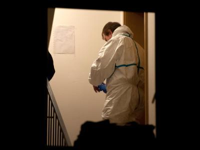 Ein Polizist der Spurensicherung steht im Treppenhaus vor einer Wohnung in Altenstadt, in der zwei Tote entdeckt wurden. Foto: Armin Weigel