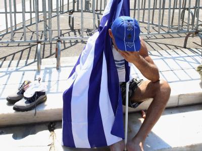 Ein Demonstrant mit einer griechischen Flagge am Rande einer Demonstration in Athen. Foto: Pantelis Saitas/Archiv