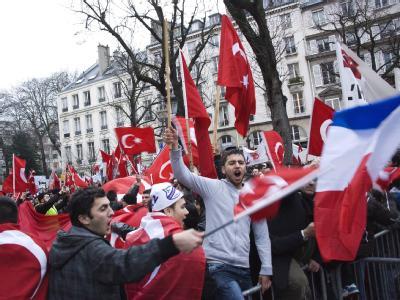 Demonstranten protestieren mit türkischen Fahnen gegen das umstrittene Völkermord-Gesetz in Paris. Foto: Emma Foster