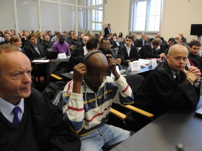 Die angeklagten zehn mutmaßlichen Piraten aus Somalia bei Prozessbeginn am 22.11.2010 mit ihren Anwälten im Gerichtssaal in Hamburg. Foto: Marcus Brandt