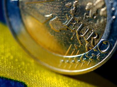 Eine Euro-Münze steht auf einer EU-Fahne. Foto: Oliver Berg/Archiv