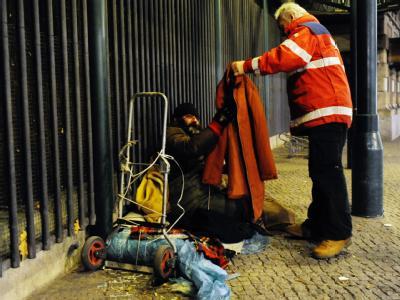 Ein Mitarbeiter der DRK-Kältehilfe kümmert sich in Berlin um einen Obdachlosen, der auf der Straße schlafen will. Foto: Maurizio Gambarini