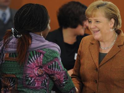 Bundeskanzlerin Angela Merkel begrüßt Virginia Wangare Greiner vom Maisha-Verein, der Selbsthilfegruppe Afrikanischer Frauen zum Integrationsgipfel. Foto: Hannibal