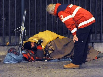 Mitarbeiter der DRK-Kältehilfe kümmern sich in Berlin um einen Obdachlosen, der auf der Straße schlafen will. Foto: Maurizio Gambarini