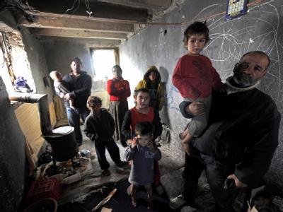 Notstand in der mazedonischen Stadt Skopje: Eine Roma-Familie versucht, sich an einem Holzofen (links) zu wärmen. Foto: Georgi Licovski