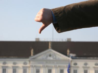 Mit einem nach unten zeigenden Daumen protestiert ein Demonstrant vor dem Schloss Bellevue in Berlin. Foto: Stephanie Pilick
