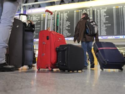 Flugreisende stehen im Terminal 1 des Flughafens von Frankfurt am Main vor einer Anzeigetafel mit den Abfluginformationen. Foto: Arne Dedert