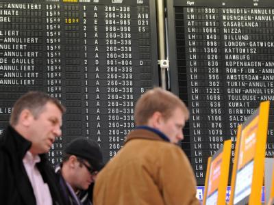 Reisende informieren sich in der Abflughalle des Frankfurter Flughafens. Foto: Arne Dedert