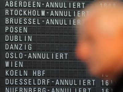 Ein Flugreisender steht in Terminal 1 des Flughafens von Frankfurt am Main vor einer Anzeigetafel, auf der annullierte Flüge angezeigt werden. Foto: Arne Dedert
