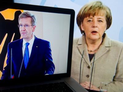 Bundespräsident Christian Wulff spricht im Schloss Bellevue in Berlin und ist dabei auf einem Laptop zu sehen im Hintergrund gibt Bundeskanzlerin Angela Merkel im Tv eine Stellungnahme ab. Foto: Stefa Sauer