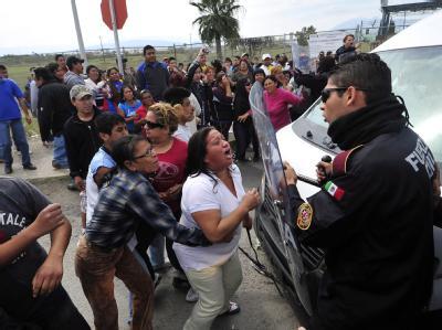 Angehörige von Gefängnisinsassen fordern Informationen von der Polizei über blutige Auseinandersetzungen in einem mexikanischen Gefängnis. Foto: Miguel Sierra