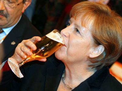 Bundeskanzlerin Angela Merkel trinkt beim Aschermittwochstreffens der CDU in Demmin ihr Bier. Foto: Jens Büttner