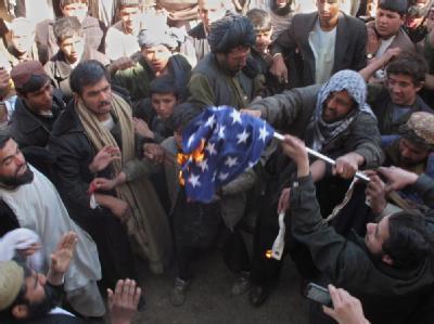Aufgebrachte Afghanen verbrennen in der Provinz Helmand eine US-Flagge. Foto: Sher Khan