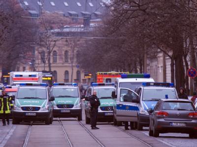 Sicherheitskräfte stehen vor der Schule in Leipzig an der es einen Amokalarm gab. Foto: Peter Endig