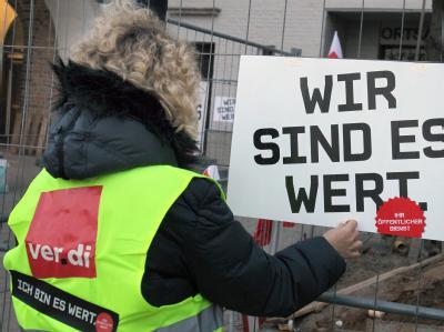Die Teilnehmerin eines Warnstreiks befestigt vor dem Rathaus in Rostock ein Schild mit einem Verdi-Slogan.  Foto: Bernd Wüstneck