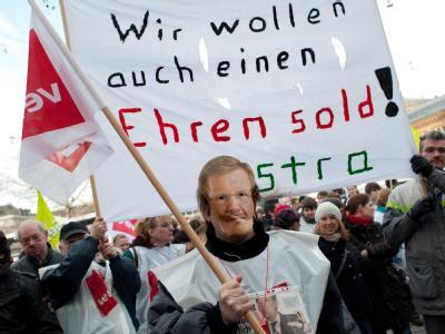 Ein streikender Angestellter mit Christian Wulff-Maske steht während eine Verdi-Kundgebung auf dem Ernst-August-Platz in Hannover. Foto: Jochen Lübke