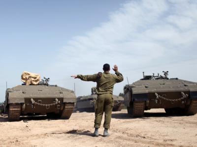 Ein israelischer Soldat dirigiert gepanzerte Fahrzeuge an der Grenze zum Gazastreifen. Foto: Abir Sultan