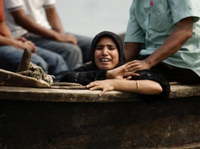 Eine Frau trauert um ihre Ehemann, der bei dem Fährunglück ums Leben gekommen ist. Foto: Abir Abdullah