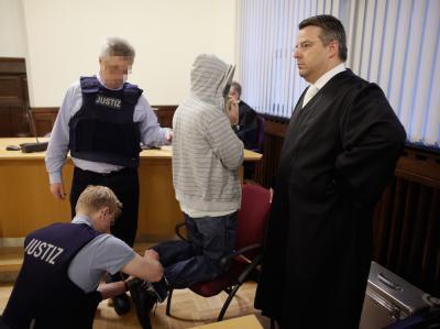 Justizvollzugsbeamte nehmen  im Gerichtssaal des Koblenzer Oberlandesgerichts dem Angeklagten Husam S. (2.v.r.) die Fußfesseln ab. Foto: Thomas Frey
