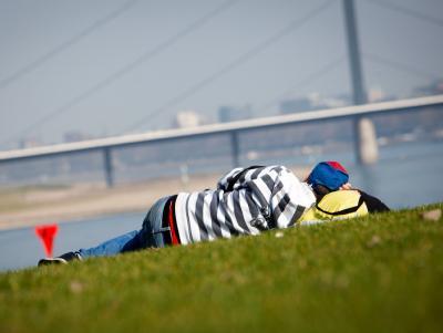 Jede Minute auskosten: Ein Mann hat es sich auf den Rheinwiesen in Düsseldorf gemütlich gemacht. Foto: Nico Kurth