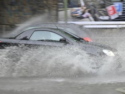 Ein Auto fährt nach einem Unwetter mit Starkregen durch eine überflutete Straße in Bochum. Foto: Marius Becker/Archiv