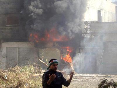 Ein Mann steht vor einem brennenden Gebäude in Homs (Syrien). Foto: LCC